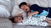 哥哥拉着宝宝的手在沙发上玩,弟弟却全程盯着镜头,好可爱啊