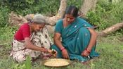 印度妇女用传统方法制作花生糖,做好后和老奶奶一起吃